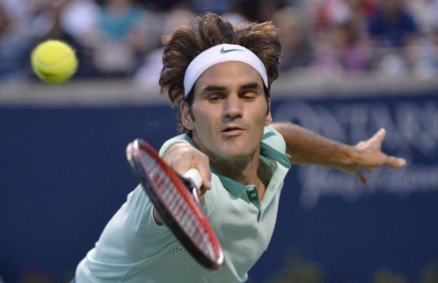 Roger Federer, of Switzerland, returns to Feliciano Lopez, of Spain, at the Rogers Cup tennis tournament, Saturday, Aug. 9, 2014 in Toronto. (AP Photo/The Canadian Press, Nathan Denette)