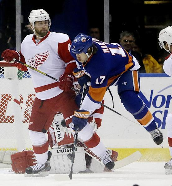 New York Islanders left wing Matt Martin (17) jumps up while trying to connect on the puck as Detroit Red Wings' Jakub Kindl, of the Czech Republic, defends on the play during the first period of an NHL hockey game, Friday, Nov. 29, 2013, in Uniondale, N.Y. (AP Photo/Julio Cortez)