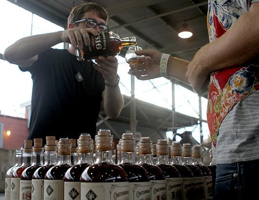 Joe Sullivan of the Chattanooga Whiskey Company pours a sample for a visitor at the Tennessee Whiskey Festival inside the First Tennessee Pavilion in Chattanooga, Tenn., Sept. 21, 2013