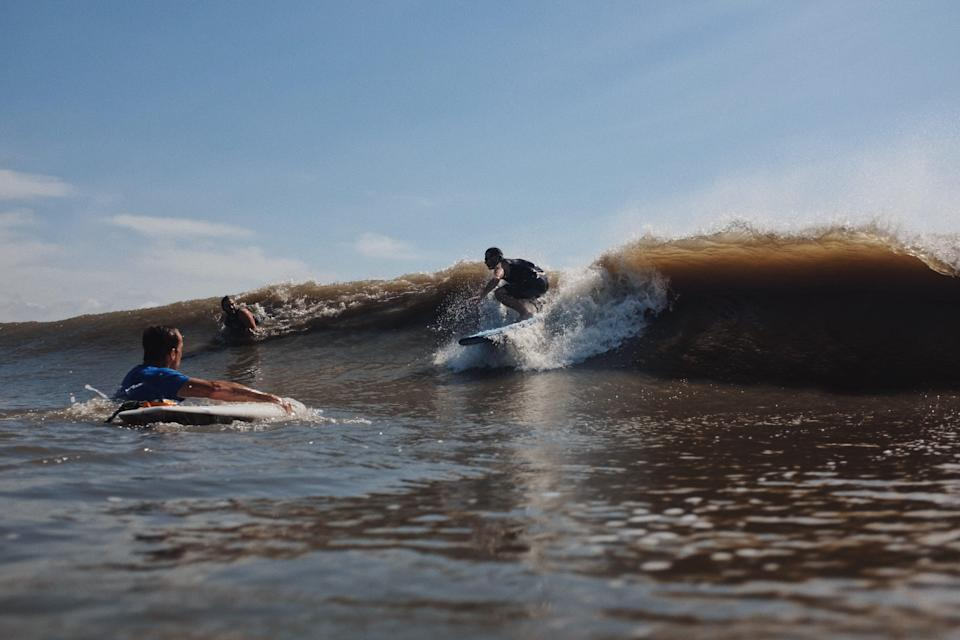 A surfer catches a wave off Grand Isle in the silty, rich water of the Gulf of Mexico