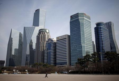 FILE PHOTO:  A man walks in a park at a business district in Seoul