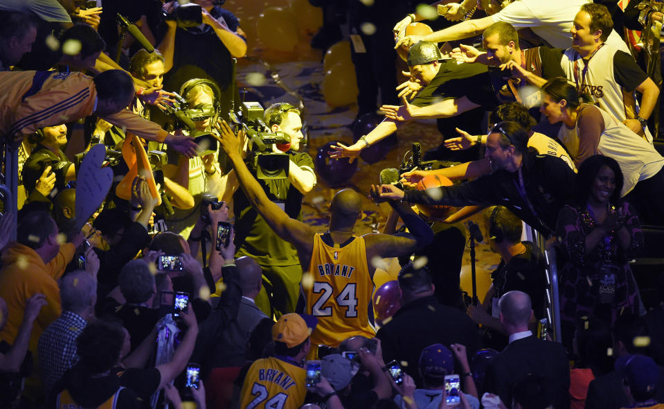 Kobe Bryant walks off the court surrounded by fans and photographers after his last NBA game before retiring on April 13, 2016.