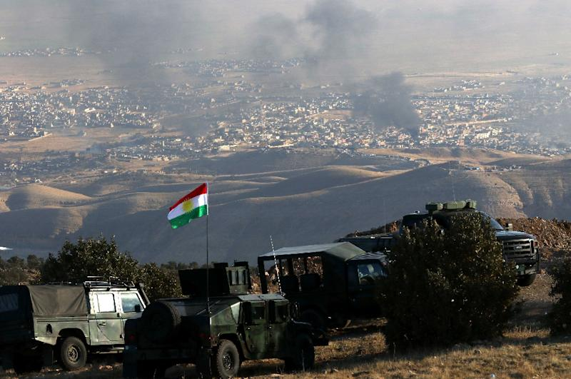 Iraqi Kurdish forces are seen stationed on a hill top as smoke billows during an operation by Iraqi Kurdish forces backed by US-led strikes in the northern Iraqi town of Sinjar, in the northern Iraqi province of Mosul, on November 12, 2015