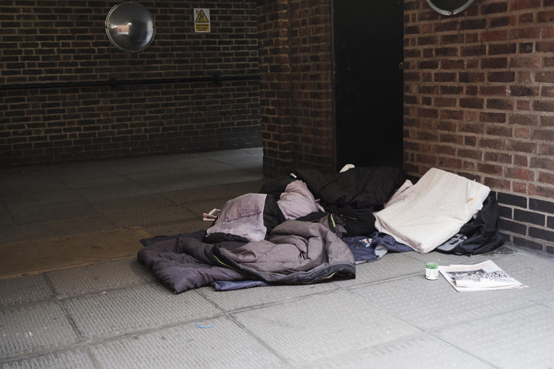 High angle view of sleeping bag on footpath by brick wall in city