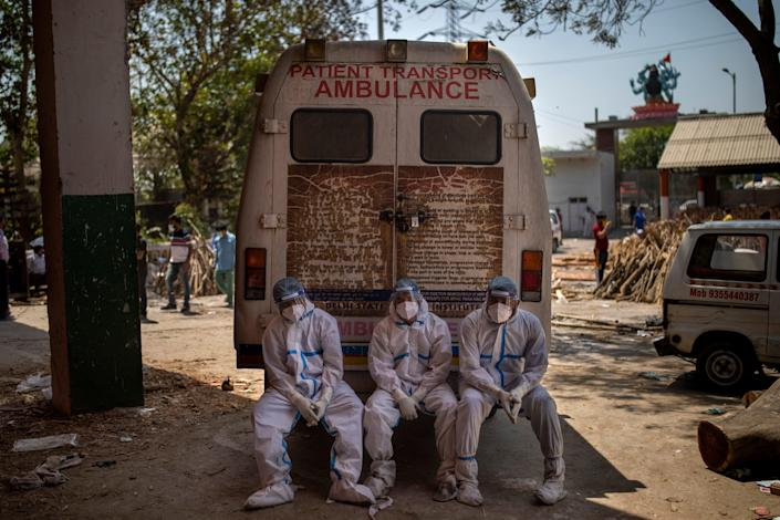 Exhausted workers, who bring dead bodies for cremation, sit on the rear step of an ambulance inside a crematorium, in New Delhi, India, Saturday, April 24, 2021.