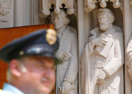 A Duke University security guard keeps watch near the defaced statue of Confederate commander General Robert E. Lee, which stands next to a statue of Thomas Jefferson, at Duke Chapel in Durham, North Carolina, U.S. on August 17, 2017.  REUTERS/Jonathan Drake