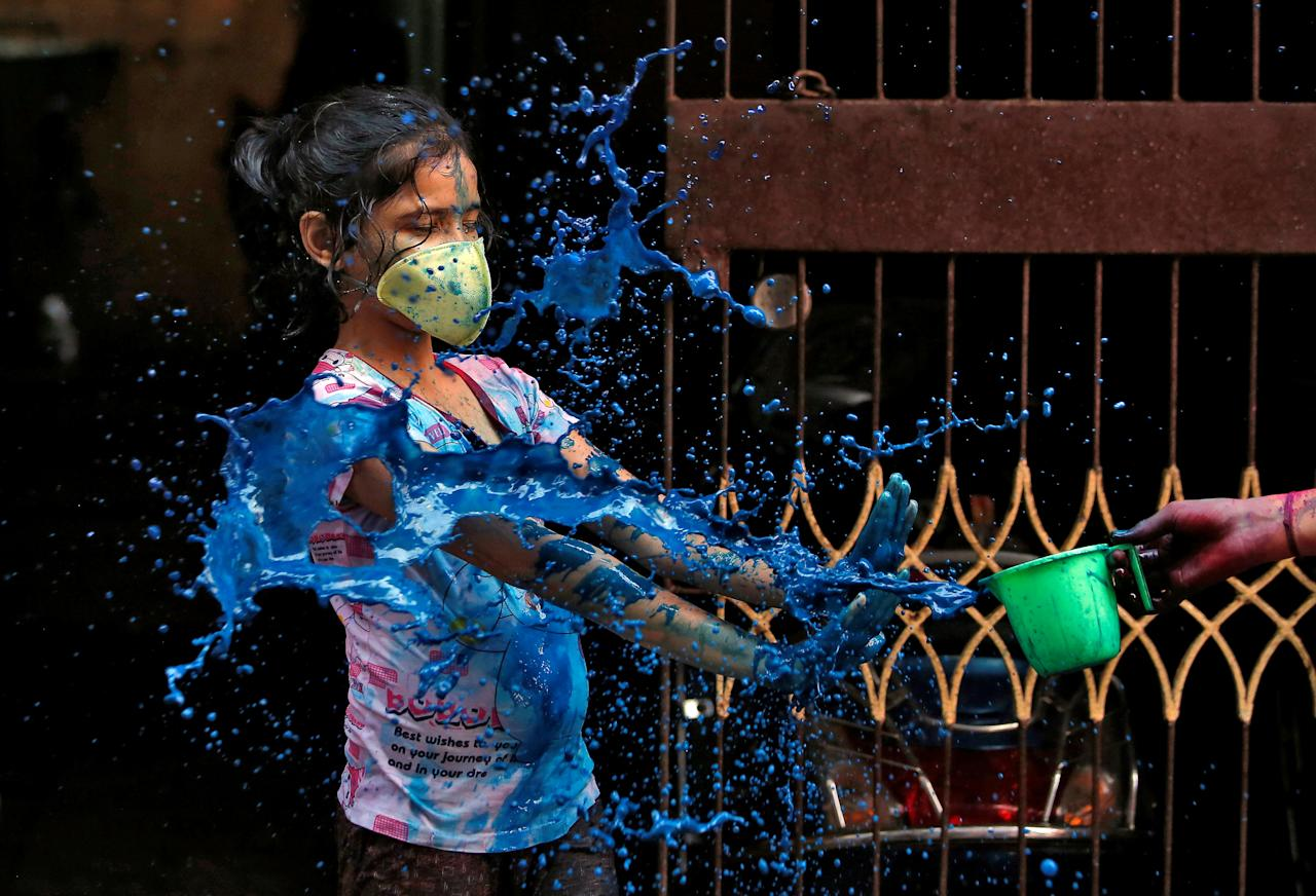 A girl wearing a protective mask reacts as she is splashed with coloured water during Holi celebrations amid coronavirus precautions, in Chennai, India, March 10, 2020. REUTERS/P. Ravikumar TPX IMAGES OF THE DAY