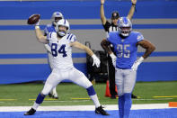 Indianapolis Colts tight end Jack Doyle (84) prepares to spike the ball next to Detroit Lions defensive end Romeo Okwara (95), after his 7-yard reception for a touchdown during the first half of an NFL football game against the Detroit Lions, Sunday, Nov. 1, 2020, in Detroit. (AP Photo/Tony Ding)