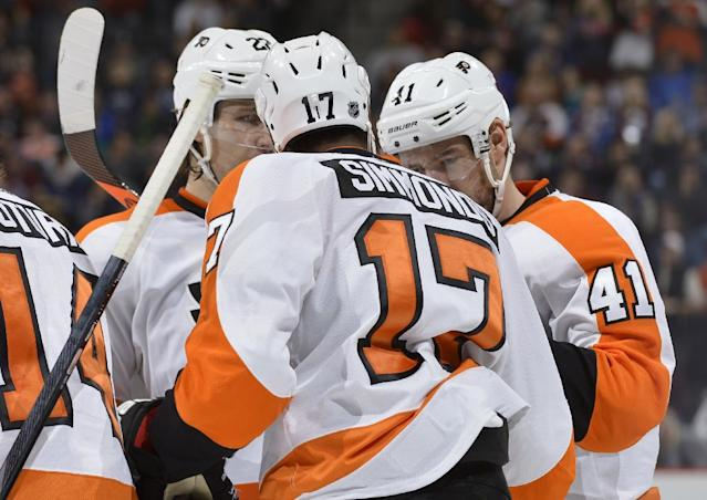 Philadelphia Flyers defenseman Luke Schenn (22) and Wayne Simmonds (17) congratulate Andrej Meszaros (41) after Meszaros scored a goal against the Colorado Avalanche during the second period of an NHL hockey game on Thursday, Jan. 2, 2014, in Denver. (AP Photo/Jack Dempsey)
