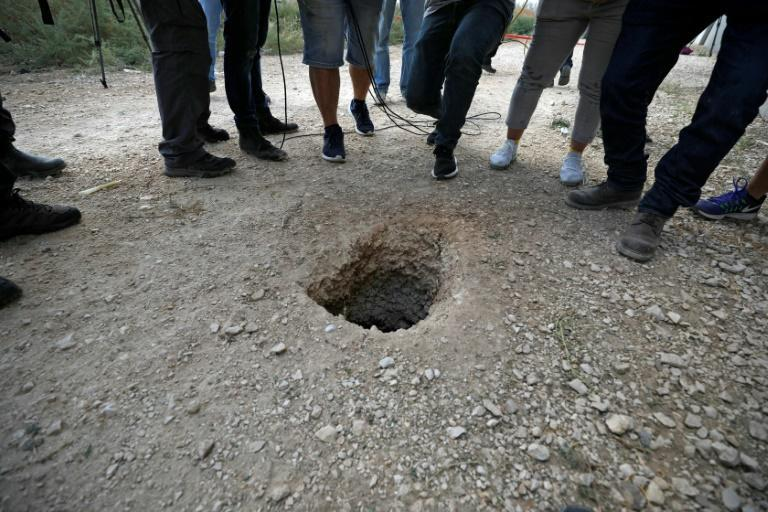 Police and journalists gather around a hole used by six Palestinian prisoners to escape from the Gilboa Prison after they dug a tunnel beneath a sink (AFP/Jalaa MAREY)
