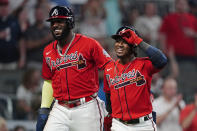 Atlanta Braves' Ozzie Albies, right, walks to the dugout with Marcell Ozuna after hitting a home run in the fifth inning of the team's baseball game against the Pittsburgh Pirates on Friday, May 21, 2021, in Atlanta. (AP Photo/John Bazemore)