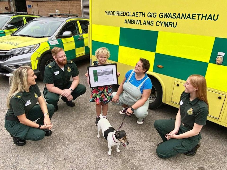 (from left) Paramedics Harriett Thomas and Will Jones, Isla, her mother Katherine Holifield, dog Roly and call handler Madison Vickery (Welsh Ambulances Services NHS Trust/PA)
