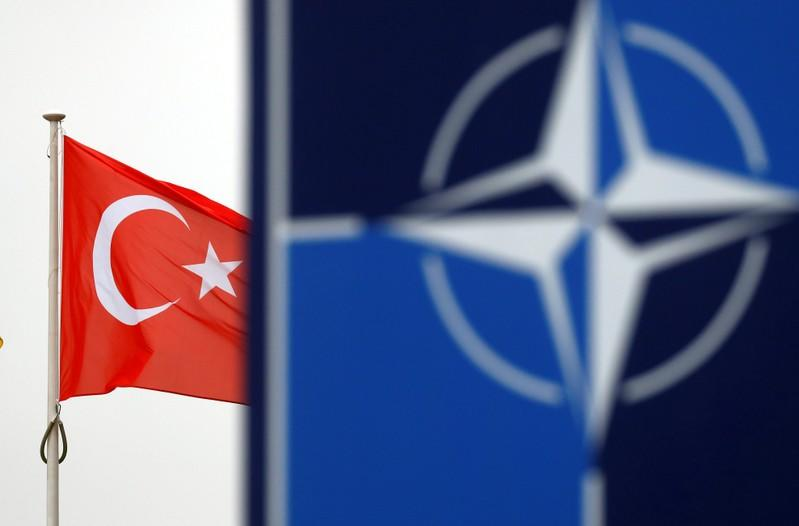 A Turkish flag flies next to NATO logo at the Alliance headquarters in Brussels