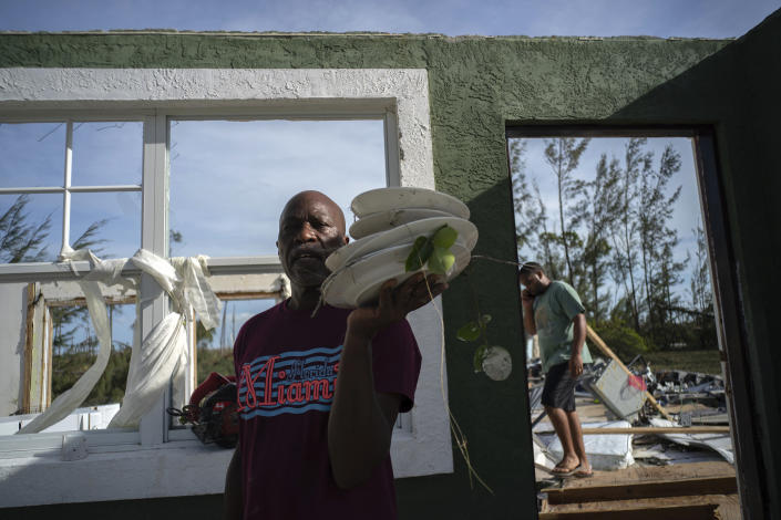 Mister Bolter recovers dishes from his son's home, destroyed by Hurricane Dorian in Pine Bay, near Freeport, Bahamas, Sept. 4, 2019. (Photo: Ramon Espinosa/AP)