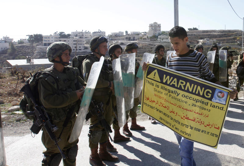 A Palestinian protester holds a placard in front of Israeli soldiers during a demonstration in the West Bank village of al-Masara near Bethlehem, marking the recognition of a sovereign Palestinian state by the United Nations. Friday Nov. 30, 2012. The United Nations General Assembly on 29 November voted 138-9 with 41 countries abstaining to upgrade the Palestinian status at the world organization to a non-member state.(AP Photo/Nasser Shiyoukhi)