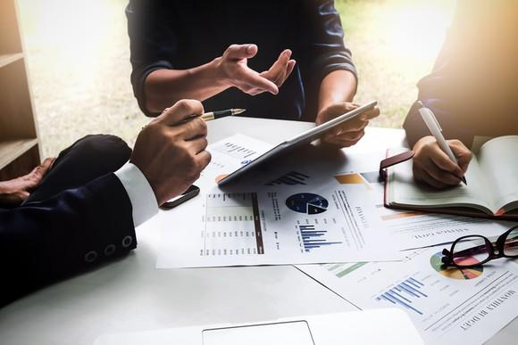 Three people sitting at a table reviewing financial charts.
