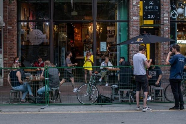 People drink and mingle on a patio in Gastown in July.