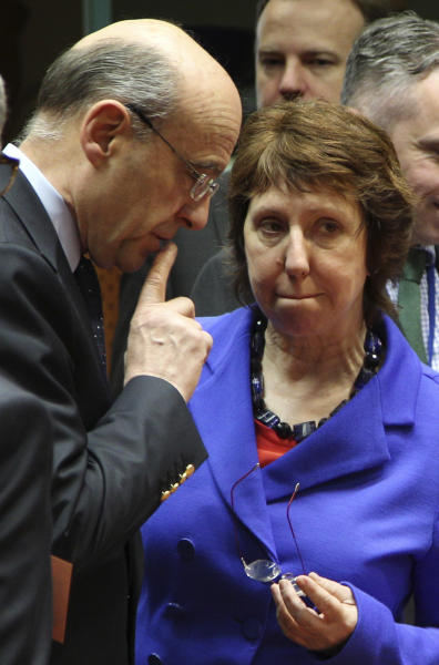 French Foreign Minister Alain Juppe, left, talks with EU foreign policy chief Catherine Ashton, prior to the start of an EU Foreign Ministers council, at the European Council building in Brussels, Friday, March 23, 2012. Officials say that the EU foreign ministers have slapped sanctions on the wife and other close relatives of Syrian President Bashar Assad in a continuing attempt to stop the violent crackdown on opposition. They said four members of the Assad family and eight government ministers have been targeted in the latest round of sanctions. (AP Photo/Yves Logghe)