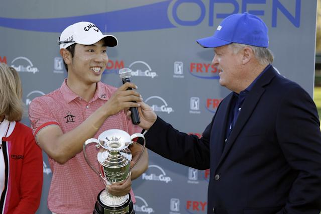 Bae Sang-Moon of South Korea, left, talks with broadcaster Johnny Miller, right, on the 18th green of the Silverado Resort North Course after winning the Frys.com PGA Tour golf tournament Sunday, Oct. 12, 2014, in Napa, Calif. Bae Sang-Moon won the tournament after shooting a 1-over-par 73 to finish at total 15-under-par. (AP Photo/Eric Risberg)
