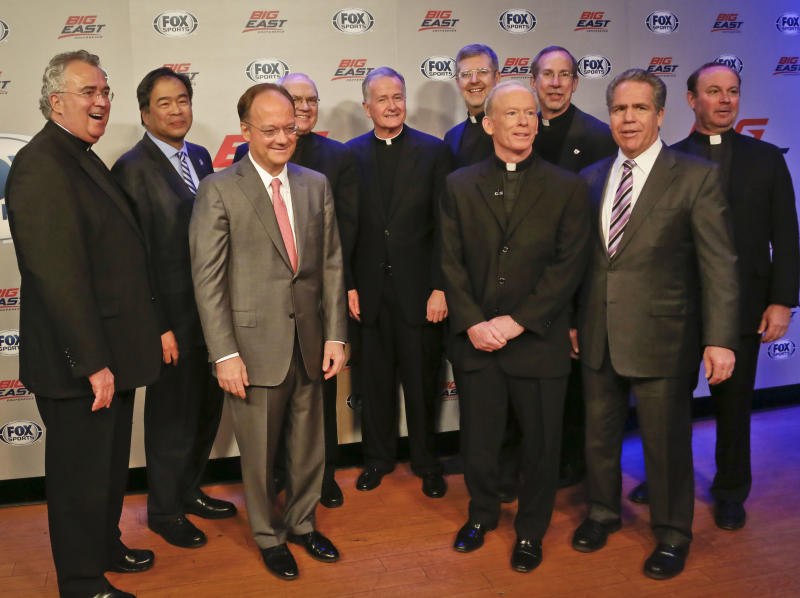 Villanova University President Rev. Peter Donohue, far left, Seton Hall University President A. Gabriel Esteban, second from left, Georgetown University President John DeGioia, third from left, St. Johns University President Donald Harrington, fourth from left, Creighton University President Rev. Timothy Lannon, fifth from left, Depaul University President Dennis Holtschneider, fifth from right, Providence University President Rev. Brian Shanley, fourth from right, Xavier University President Michael Graham, third from right, Butler University President Jim Danko, second from right, and Marquette University President Rev. Scott Pilarz, far right, assemble for a photo following a press conference on Wednesday, March 20, 2013 in New York.   Big East athletic conference member schools gathered in New York to announce developments helping to shape the new basketball-focused conference.  (AP Photo/Bebeto Matthews)