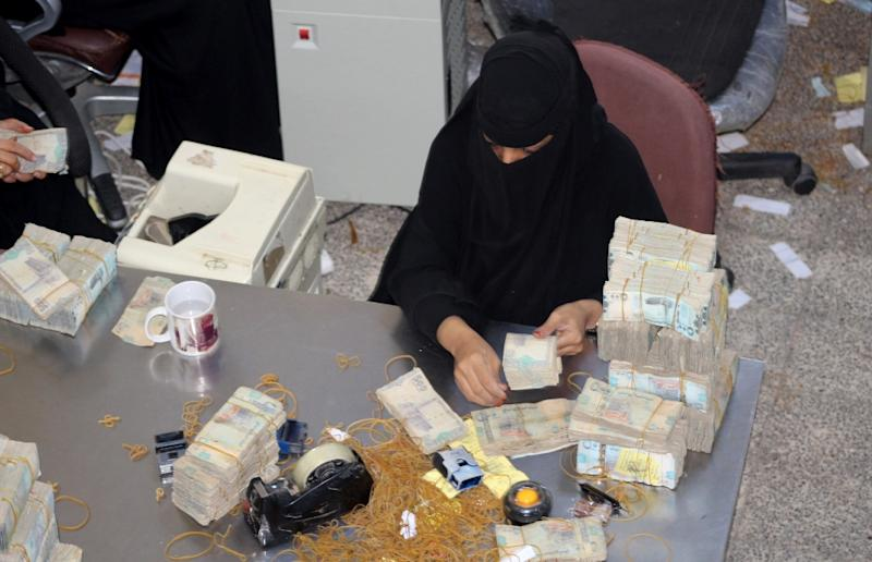 A bank teller counts money at the Central Bank of Aden in Aden on December 13, 2018 (AFP Photo/Saleh Al-OBEIDI)