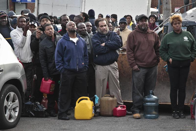 A crowd gather at a service station with portable containers, waiting for gas pumps to open, Saturday, Nov. 3, 2012 in the Brooklyn borough of New York.  Mayor Michael Bloomberg said that resolving gas shortages could take days.  Police presence was increased at gas lines after arrests at gas stations over line jumping. (AP Photo/Bebeto Matthews)
