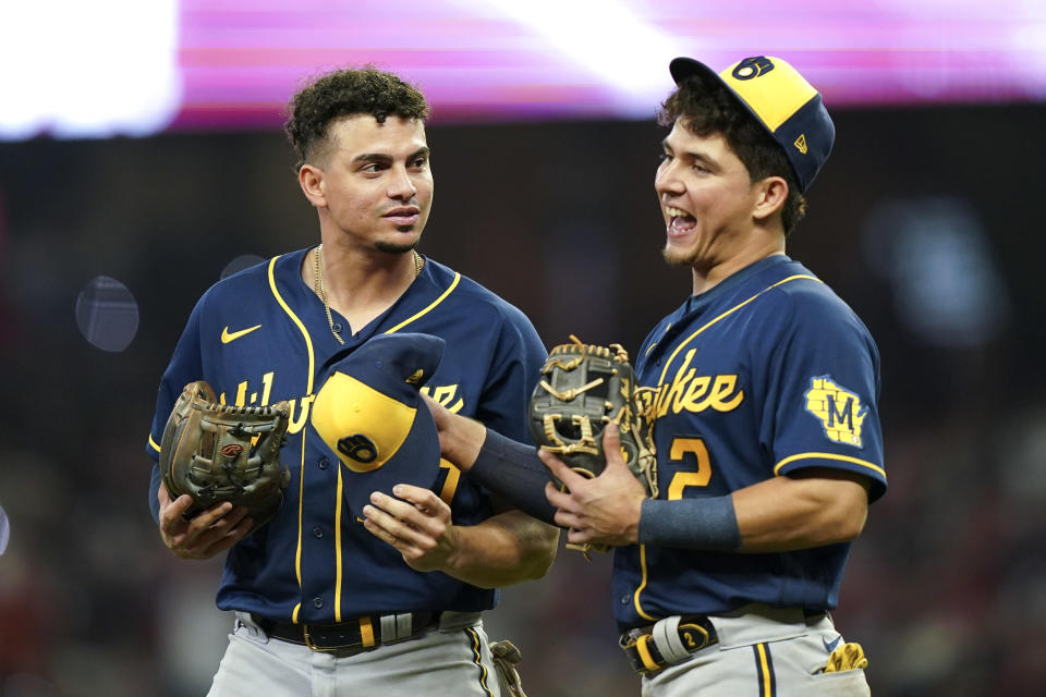 Milwaukee Brewers shortstop Willy Adames, left, speaks with Milwaukee Brewers third baseman Luis Urias during the seventh inning of Game 4 of a baseball National League Division Series against the Atlanta Braves , Tuesday, Oct. 12, 2021, in Atlanta. (AP Photo/Brynn Anderson)