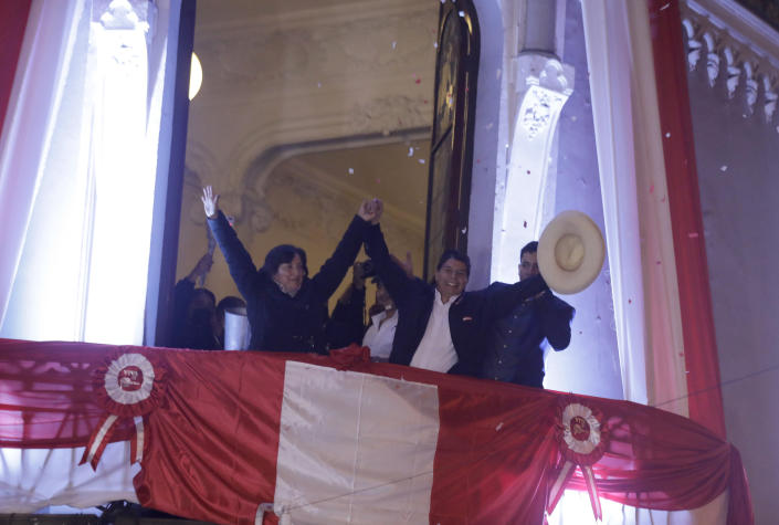 Pedro Castillo, center, celebrates with his running mate Dina Boluarte after being declared President of Peru by election authorities in Lima Peru, Monday, July 19, 2021. Castillo was declared president more than a month after the elections took place and after opponent Keiko Fujimori claimed that the election was tainted by fraud. (AP Photo/Guadalupe Prado)
