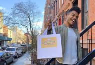 """Broadway performer Max Kumangai holds a bag promoting his company Humpday Dough in New York. The triple threat from the musical """"Jagged Little Pill"""" has leaned into a fourth skill as the pandemic marches on: baking and selling his own sourdough. (Michael Lowney/Humpday Dough via AP)"""