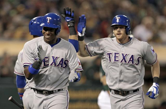 Texas Rangers' Jurickson Profar, left, celebrates after hitting a two run home run off Oakland Athletics' Tommy Milone in the fourth inning of a baseball game, Friday, Aug. 2, 2013, in Oakland, Calif. At right is Rangers' Craig Gentry. (AP Photo/Ben Margot)