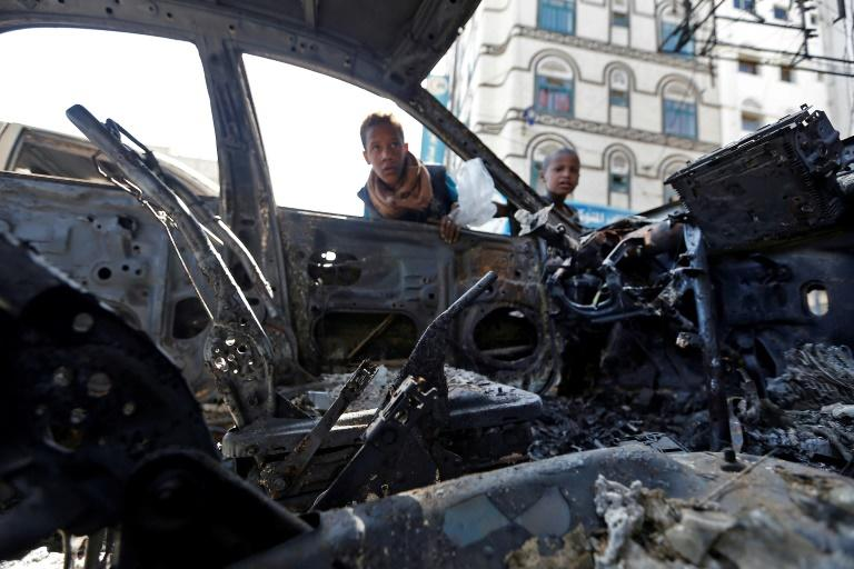 Yemeni boys peer inside a car burnt out in the deadly battle for the capital Sanaa between Huthi rebels and loyalists of ex-president Ali Abdullah Saleh