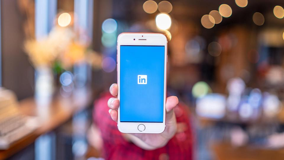 woman holding up smartphone with LinkedIn app