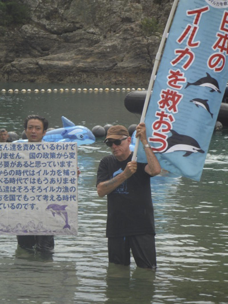 """In this Monday, Sept. 1, 2013 photo released by Dolphin Project, Ric O'Barry, right, holds a banner reading: """"Save Dolphins in Japan"""" as he joins Japanese activist Satoshi Komiyama with an anti-dolphin hunt message in Taiji, central Japan. O'Barry and former Guns N' Roses drummer Matt Sorum were in the Japanese fishing village Monday to protest against its annual dolphin hunt. Sorum, who now leads his own group, is the latest celebrity to join the increasingly global campaign to stop the dolphin kill in Taiji, a quaint fishing village made famous by O'Barry's Academy Award-winning 2009 film about the hunt called """"The Cove."""" (AP Photo/Dolphin Project)"""