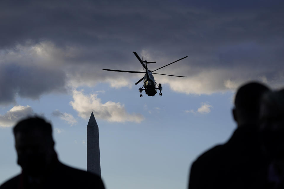 FILE - People watch as Marine One with President Donald Trump on board departs on the South Lawn of the White House, Wednesday, Jan. 20, 2021, in Washington. On Friday, Jan. 22, The Associated Press reported on stories circulating online incorrectly claiming an Army band played 'Hit the Road Jack' outside the White House before former President Donald Trump departed Washington. (AP Photo/Alex Brandon, File)