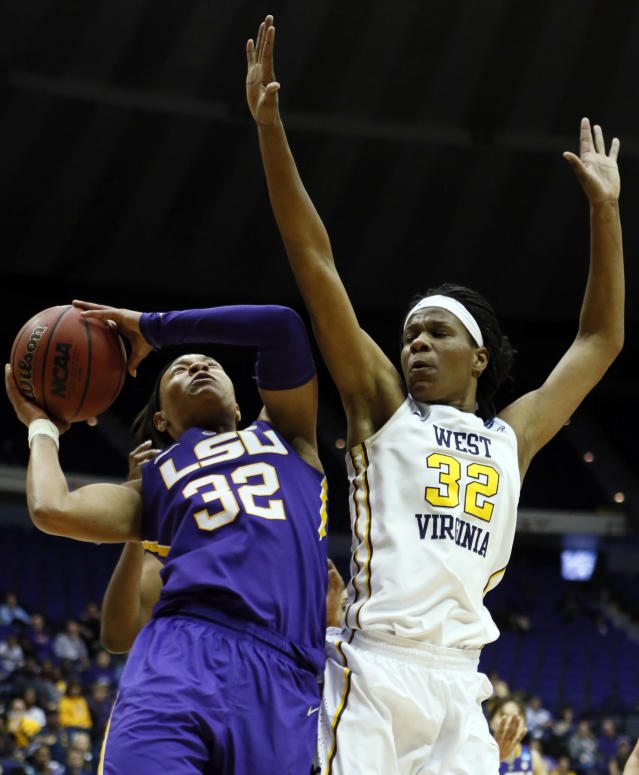 LSU guard Danielle Ballard (32) tries to shoot a layup past the defense of West Virginia forward Crystal Leary (32) in the second half of an NCAA college basketball second-round tournament game Tuesday, March 25, 2014, in Baton Rouge, La. LSU won 76-67. (AP Photo/Rogelio V. Solis)