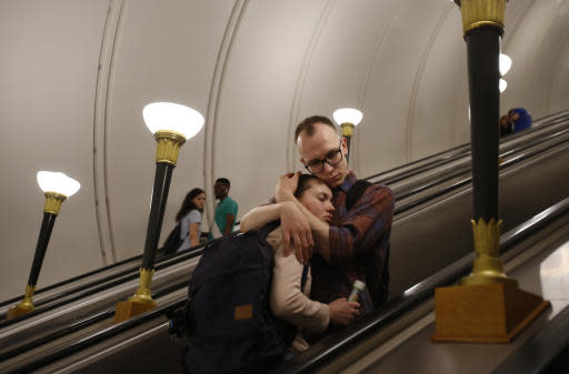 In this June 16, 2018 photo a couple embraces as they ride the escalator up to exit from the subway, during the 2018 soccer World Cup in Moscow, Russia. (AP Photo/Rebecca Blackwell)