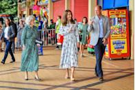 """<p>For a visit to South Wales, Kate chose an Emilia Wickstead belted, floral midi dress. She paired the look with brown suede espadrilles and, when she was indoors, her liberty print face mask. Luckily, the dress proved flexible enough for Kate to engage in some <a href=""""https://www.townandcountrymag.com/society/tradition/a33521295/kate-middleton-prince-william-arcade-games-barry-island-video-photos/"""" rel=""""nofollow noopener"""" target=""""_blank"""" data-ylk=""""slk:intense arcade games"""" class=""""link rapid-noclick-resp"""">intense arcade games</a>. </p>"""