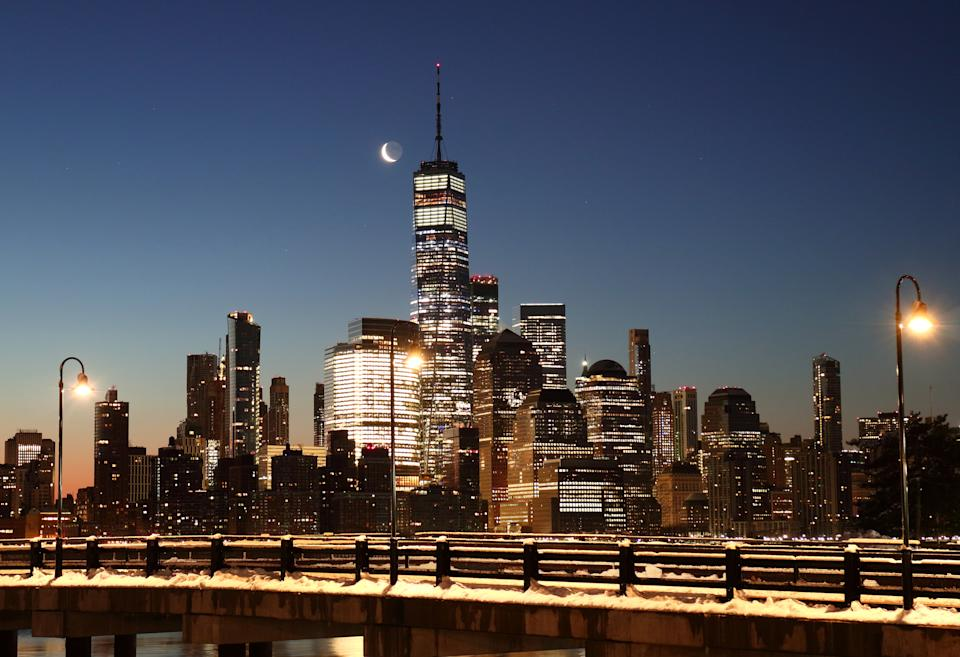 The moon rises in the pre-dawn sky above lower Manhattan and One World Trade Center in New York City. Photo: Gary Hershorn/Getty Images
