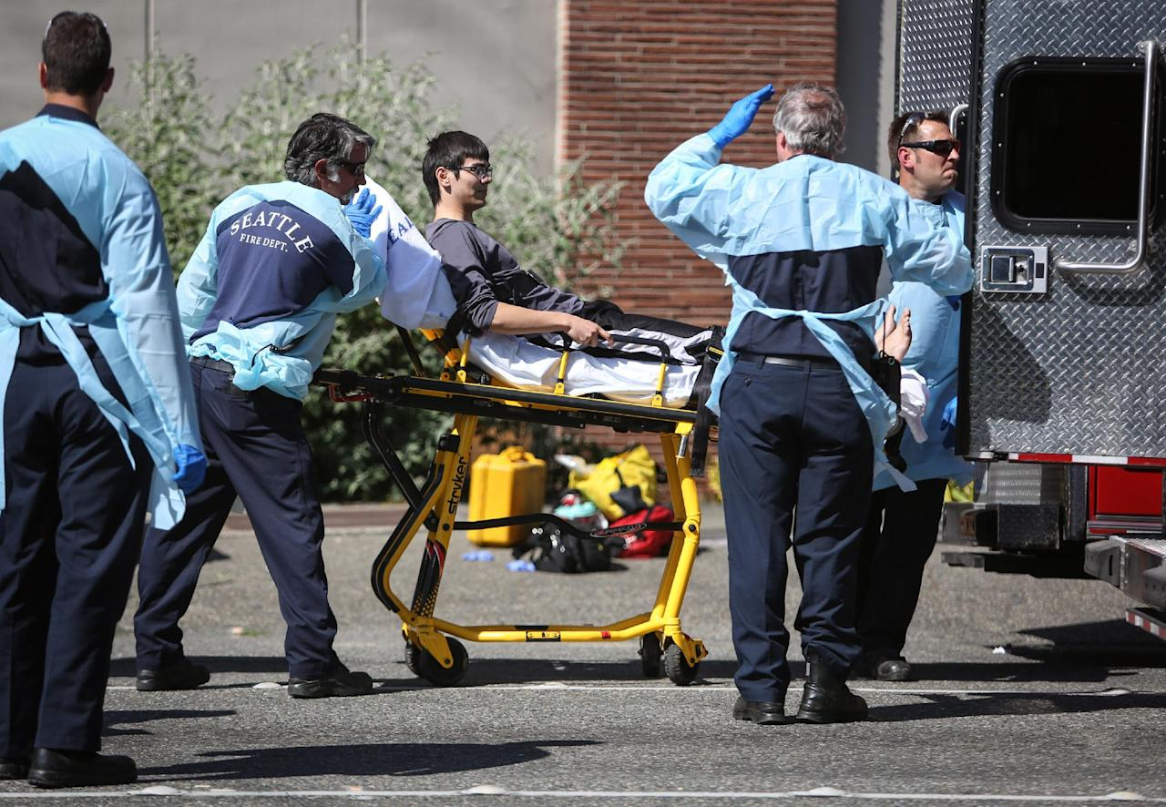 Jon Meis is taken from the scene by medics after a shooting at Seattle Pacific University on Thursday, June 5, 2014 in Seattle. A 19-year-old man was fatally shot and two other young people were wounded after a gunman entered the foyer at Otto Miller Hall on the Seattle Pacific University campus and started shooting Thursday afternoon. When he paused to reload, a student building monitor disarmed him. Meis is the student monitor who is credited with stopping the suspected gunman, Aaron R. Ybarra, 26, by pepper spraying him and tackling him. (AP Photo/seattlepi.com, Joshua Trujillo) MAGS OUT; NO SALES; SEATTLE TIMES OUT; TV OUT; MANDATORY CREDIT