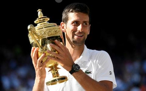 Serbia's Novak Djokovic celebrates with the trophy after winning the men's singles final against South Africa's Kevin Anderson at Wimbledon - Credit: REUTERS