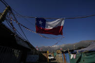 """A Chilean flag hangs inside a camp where migrants from Haiti, Peru and Colombia, set up a homes and call """"Dignidad,"""" or Dignity, in Santiago, Chile, Thursday, Sept. 30, 2021. There are 180,000 Haitians in Chile, of whom """"almost 70,000 reside in the country permanently,"""" said deputy interior minister Juan Francisco Galli. (AP Photo/Esteban Felix)"""
