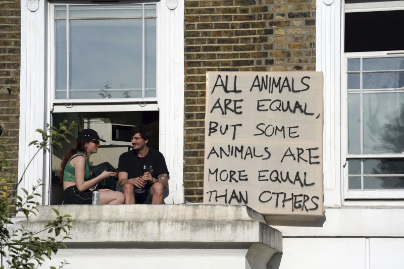 Protesters hang out a sign in the same street of where Prime Minister Boris Johnson's senior aide Dominic Cummings has his north London home after he gave a press conference over allegations he breached coronavirus lockdown restrictions, Monday May 25, 2020. (Aaron Chown/PA via AP)