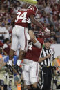 Alabama offensive lineman Jedrick Wills Jr. (74) lifts running back Damien Harris (34) after Harris scored a touchdown during the first half of the Orange Bowl NCAA college football game against Oklahoma, Saturday, Dec. 29, 2018, in Miami Gardens, Fla. (AP Photo/Lynne Sladky)
