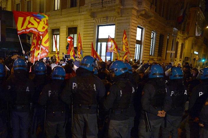"""Policemen stand guard as supporters of """"NO"""" celebrate near the Palazzo Chigi, on December 4, 2016 (AFP Photo/Filippo MONTEFORTE )"""