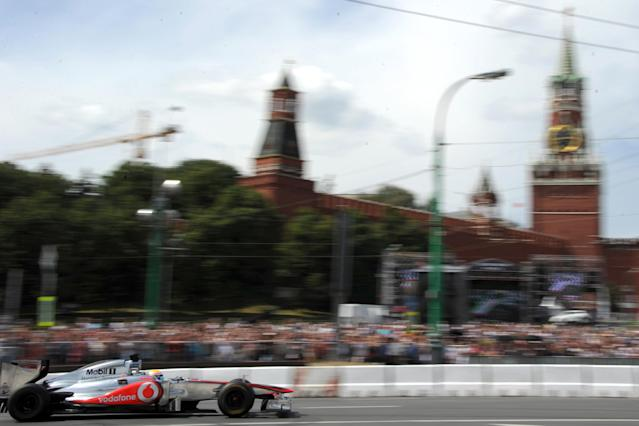 """Formula One McLaren Mercedes' British driver Lewis Hamilton speeds near the Kremlin during the """"Moscow City Racing"""" show on July 15, 2012 in central Moscow. AFP PHOTO / KIRILL KUDRYAVTSEVKIRILL KUDRYAVTSEV/AFP/GettyImages"""