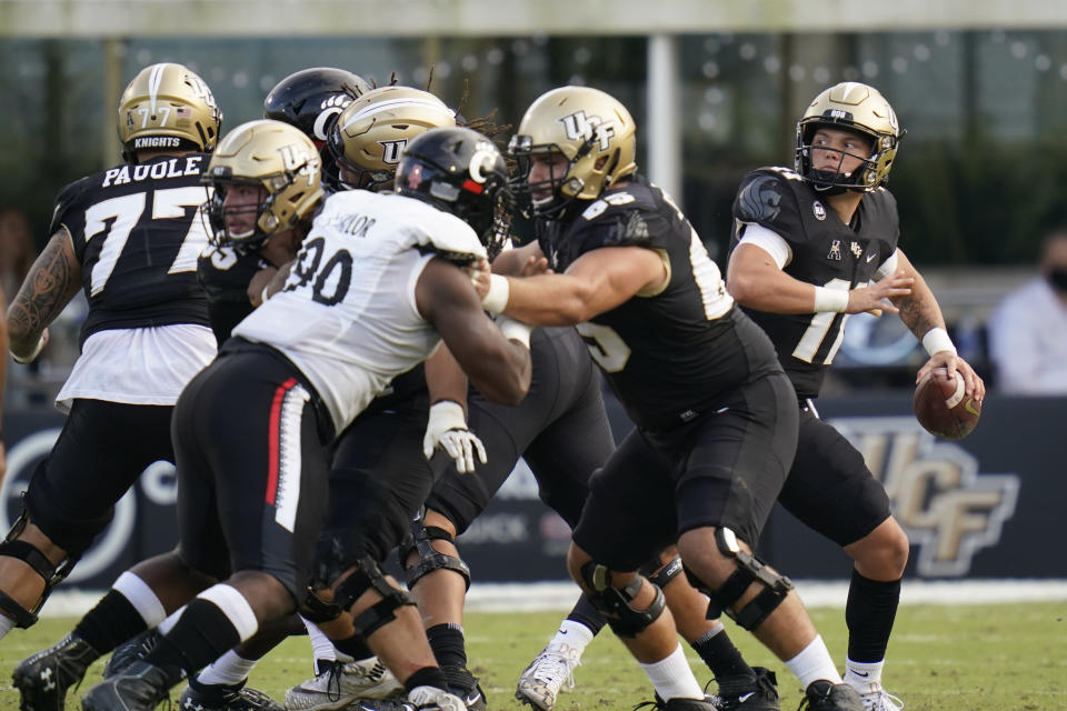 Central Florida quarterback Dillon Gabriel, far right, throws a pass against Cincinnati during the first half of an NCAA college football game, Saturday, Nov. 21, 2020, in Orlando, Fla. (AP Photo/John Raoux)