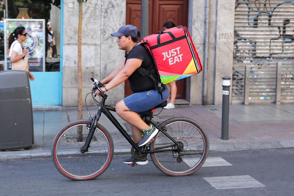 A distributor of Just Eat rides his bike with a package with food on a street on July 31, 2019 in Madrid, Spain. Photo: Jesús Hellín/Europa Press via Getty Images