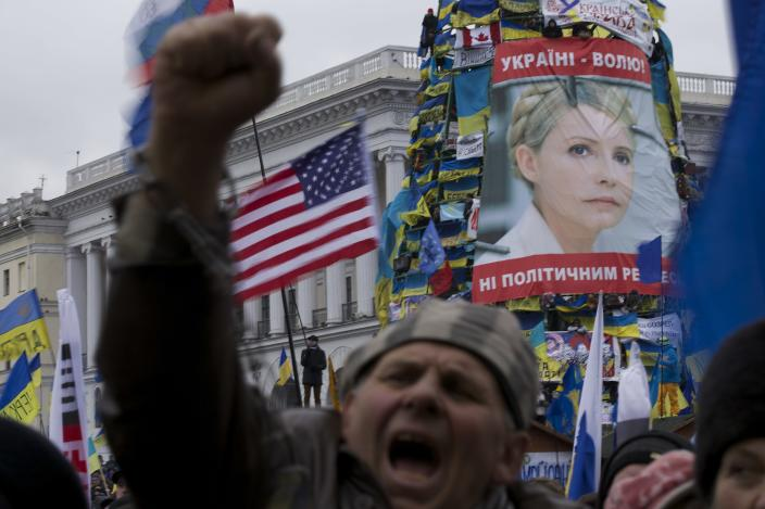 Pro-European Union activists shout slogans during a rally in Independence Square in Kiev, Ukraine, Sunday, Dec. 8, 2013 with a U.S. national flag and poster of jailed former Ukrainian Prime Minister Yulia Tymoshenko. Hundreds of thousands of Ukrainians rallied in the center of Kiev on Sunday in the biggest protest since the 2004 pro-democracy Orange Revolution, denouncing President Viktor Yanukovych's decision to turn away from Europe and raising the stakes in a tense political standoff gripping this ex-Soviet republic. (AP Photo/Alexander Zemlianichenko)