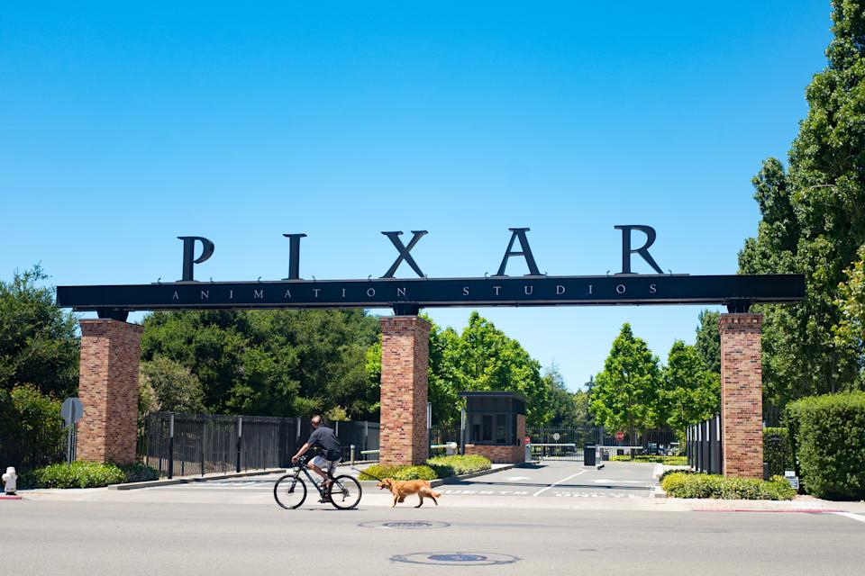 A man rides his bicycle and walks his dog past the entry gates at the headquarters of Pixar Animation Studios in downtown Emeryville, California, with logo visible, June 12, 2018. (Photo by Smith Collection/Gado/Getty Images)
