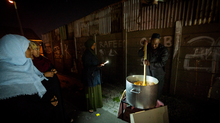 Sheikh Sameeg stirring a large pot of food in Manenberg, Cape Town - South Africa